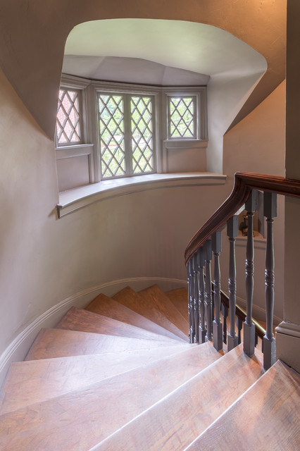 Elegant wooden curved wood railing staircase photo in Other with wooden risers
