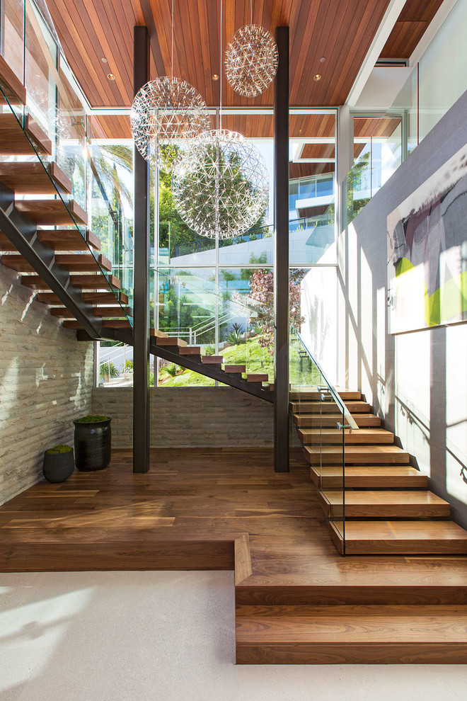 Huge trendy wooden u-shaped glass railing staircase photo in Los Angeles with wooden risers