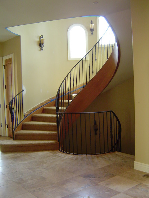 Sweeping 3 Story Staircase With Arched Windows