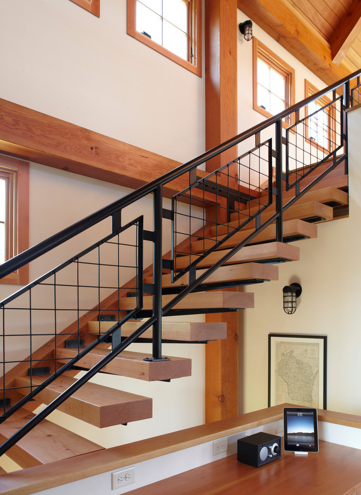 Example of a country floating open and metal railing staircase design in Milwaukee