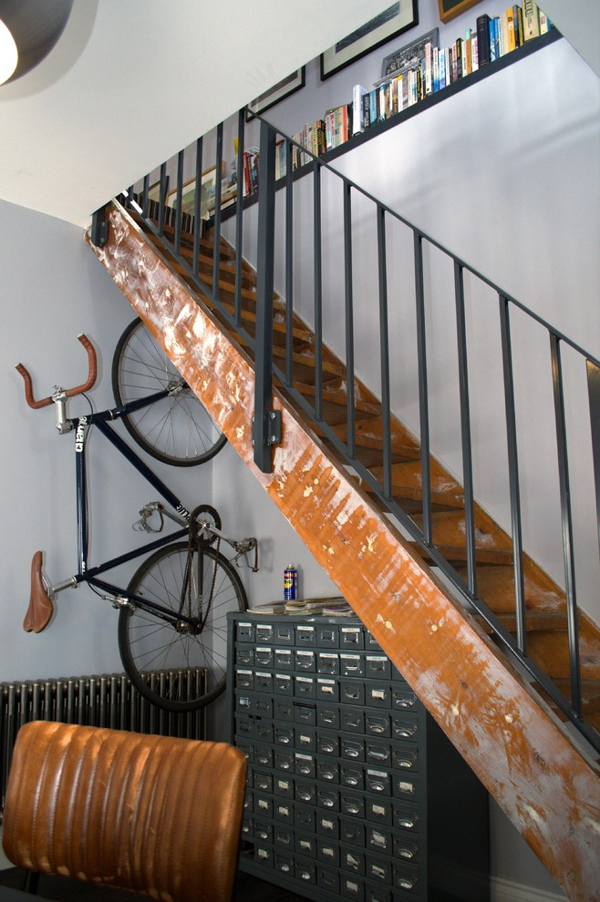 Small urban wooden straight open and metal railing staircase photo in Other