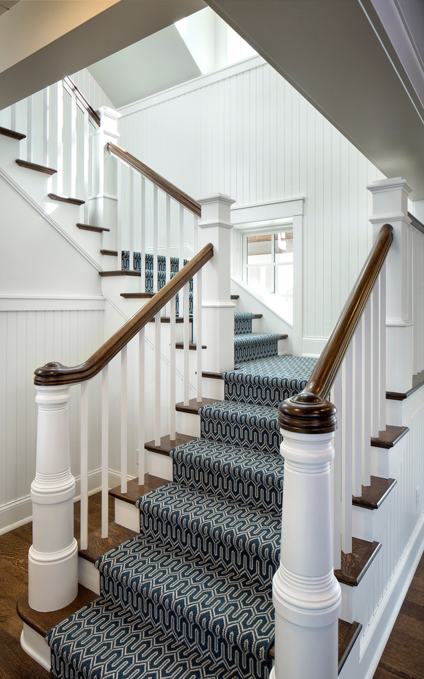 Example of a classic wooden u-shaped staircase design in Minneapolis with painted risers