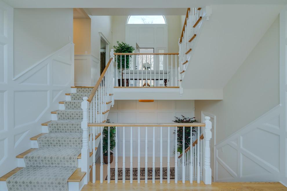 Idée de décoration pour un très grand escalier tradition en U avec des marches en bois, des contremarches en bois et un garde-corps en bois.