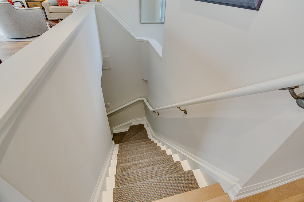 Staircase - mid-sized transitional carpeted curved wood railing staircase idea in Toronto with carpeted risers