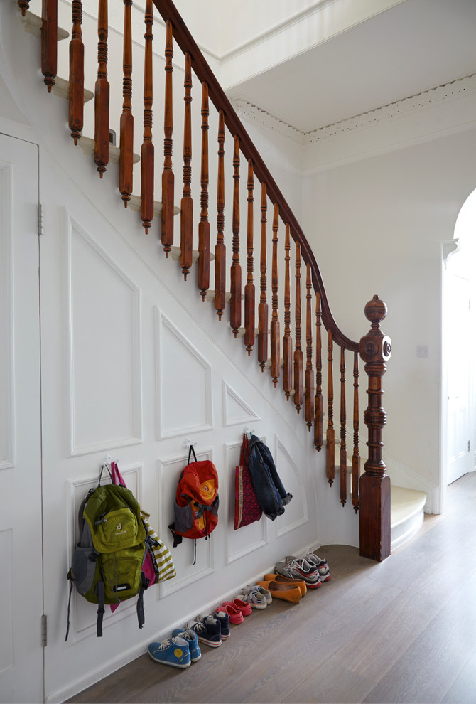Example of an ornate painted l-shaped staircase design in London with painted risers