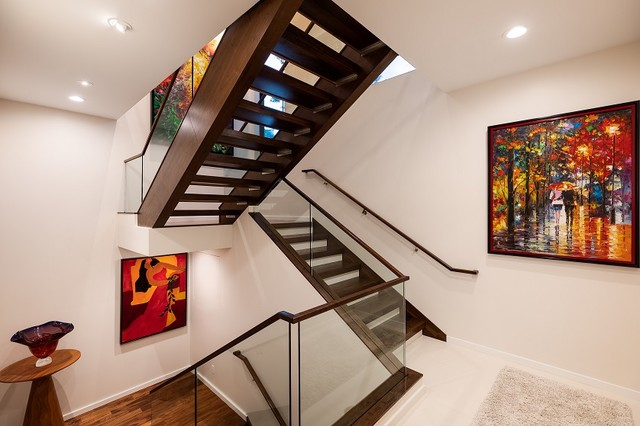 Large minimalist wooden u-shaped open and glass railing staircase photo in Hawaii