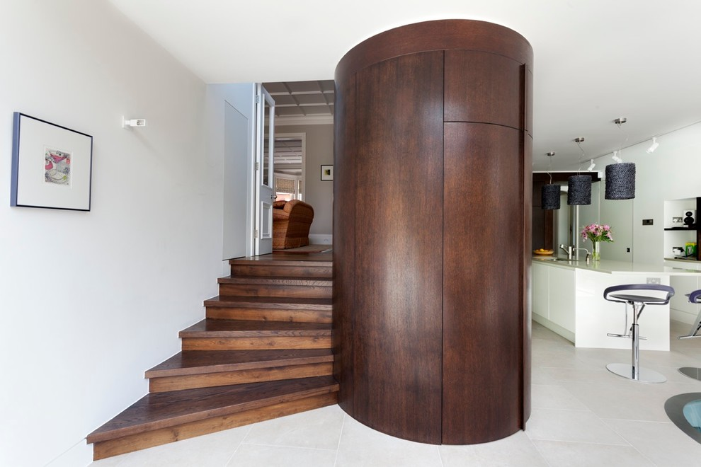 Mid-sized trendy wooden spiral staircase photo in London with wooden risers