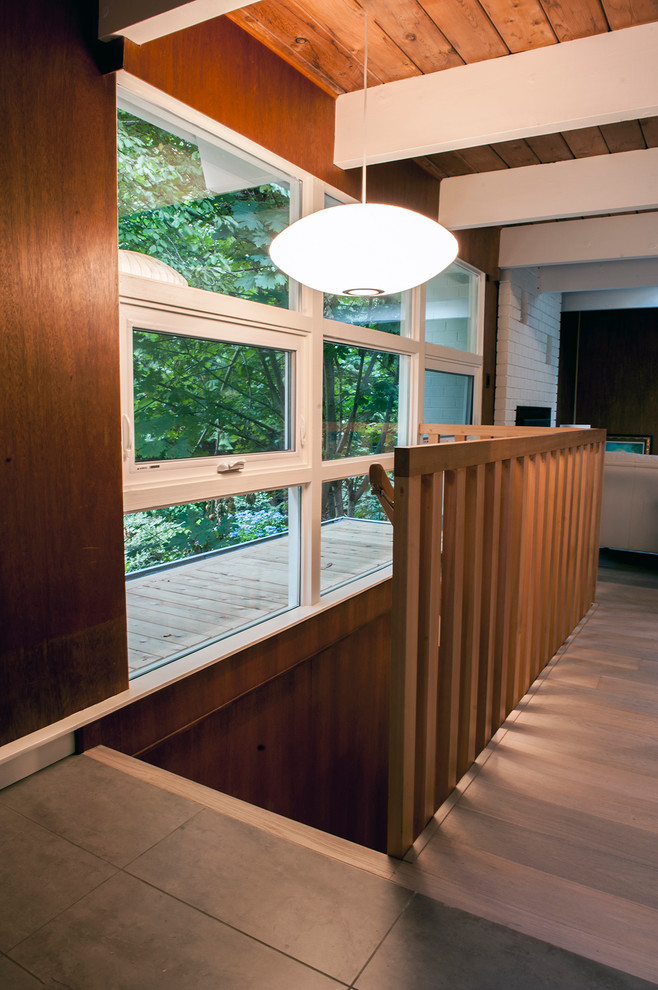 Inspiration for a mid-sized mid-century modern wooden straight staircase remodel in Vancouver with wooden risers
