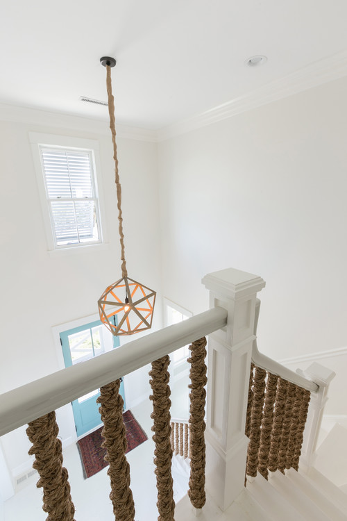 White Home With Blue Entry Foyer and Rope Staircase