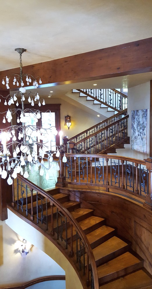 Huge mountain style wooden curved staircase photo in Salt Lake City with wooden risers