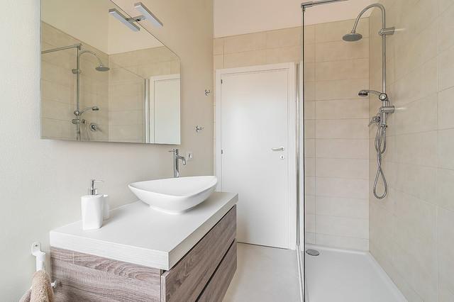 Foto di una stanza da bagno con doccia minimal di medie dimensioni con ante lisce, ante in legno chiaro, doccia ad angolo, piastrelle beige, piastrelle in gres porcellanato, pareti beige, top in legno e doccia aperta