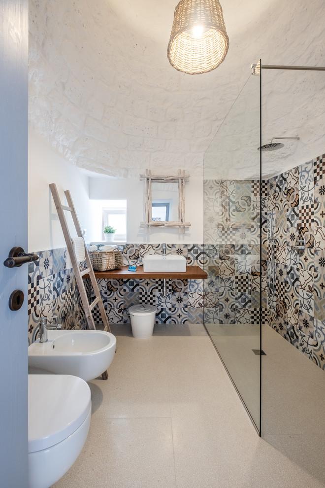 Immagine di una stanza da bagno con doccia mediterranea con doccia ad angolo, bidè, piastrelle multicolore, piastrelle di cemento, pareti bianche, lavabo a bacinella, top in legno, pavimento beige, doccia aperta e top marrone