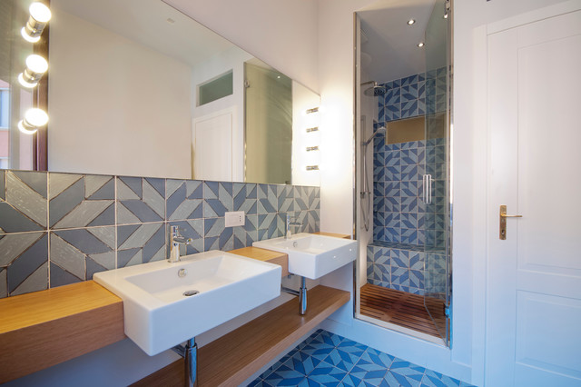 Photo of a medium sized coastal shower room in Milan with light wood cabinets, an alcove shower, multi-coloured tiles, ceramic tiles, white walls, ceramic flooring, a trough sink, wooden worktops and a hinged door.