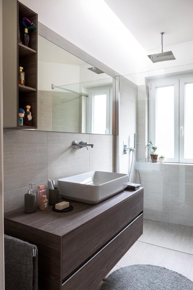 Esempio di una stanza da bagno contemporanea con ante lisce, ante in legno bruno, doccia a filo pavimento, piastrelle beige, piastrelle grigie, pareti bianche, lavabo a bacinella, top in legno, pavimento beige e top marrone
