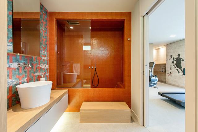 Immagine di una stanza da bagno contemporanea con lavabo a bacinella, ante lisce, ante bianche, vasca ad alcova, vasca/doccia, piastrelle arancioni, piastrelle a mosaico e pareti beige