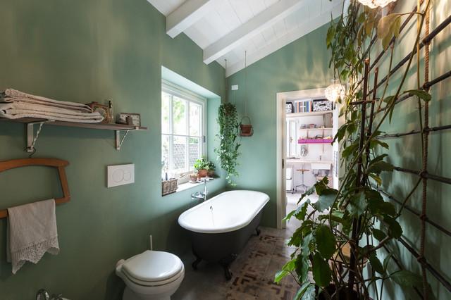 Cette image montre une salle de bain principale rustique avec une baignoire sur pieds, un WC à poser et un mur vert.