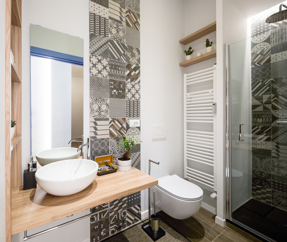 Bathroom - small contemporary 3/4 gray tile gray floor bathroom idea in Milan with open cabinets, light wood cabinets, wood countertops, a wall-mount toilet, white walls, a vessel sink, a hinged shower door and brown countertops