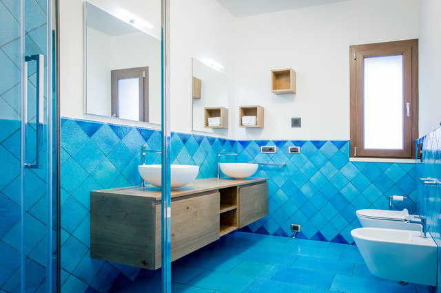 Coastal blue floor corner shower photo in Cagliari with flat-panel cabinets, medium tone wood cabinets, a wall-mount toilet, white walls, a vessel sink, wood countertops, a hinged shower door and brown countertops