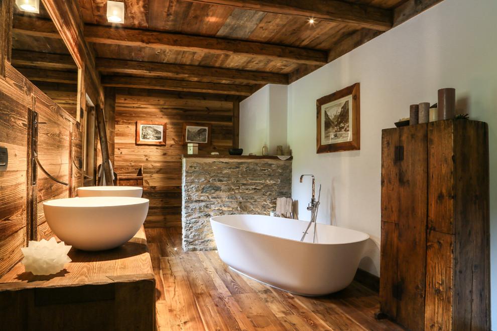 Immagine di una grande stanza da bagno padronale rustica con ante lisce, vasca freestanding, pavimento in legno massello medio, lavabo a bacinella, ante in legno bruno, pareti marroni, top in legno, pavimento marrone e top marrone