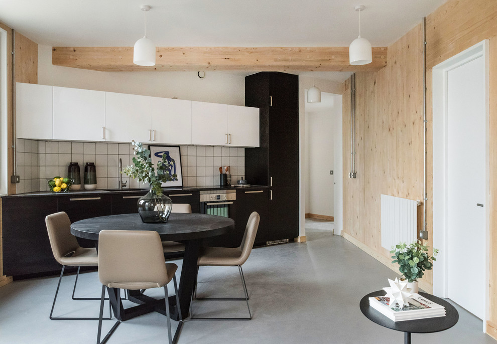 Example of a mid-sized danish concrete floor and gray floor kitchen/dining room combo design in London with white walls