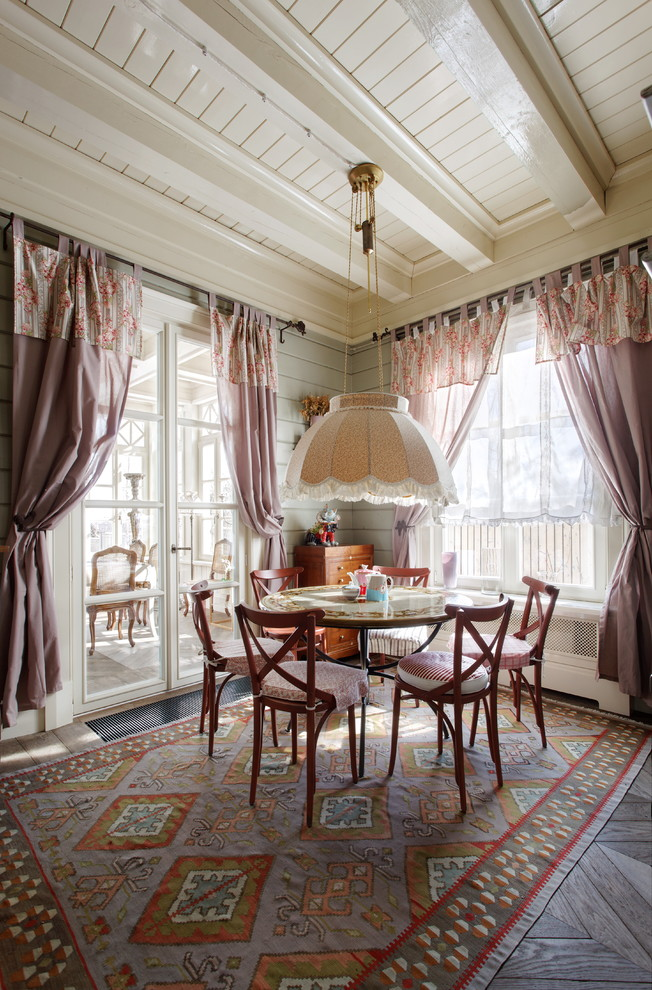 Example of a mid-sized country medium tone wood floor enclosed dining room design in Moscow with gray walls