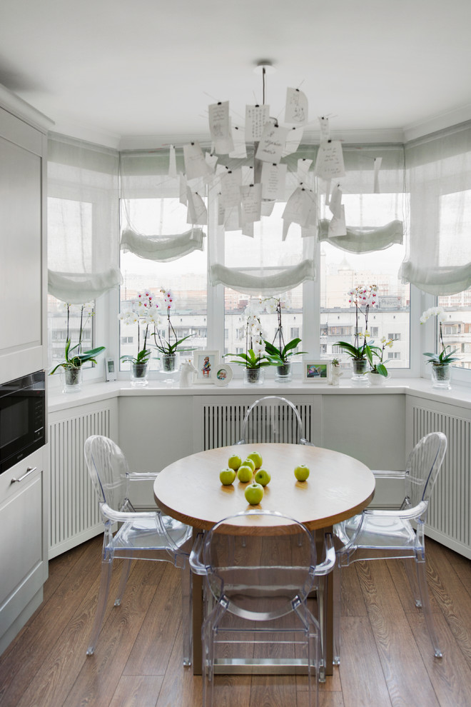 Kitchen/dining room combo - mid-sized contemporary medium tone wood floor kitchen/dining room combo idea in Moscow with white walls