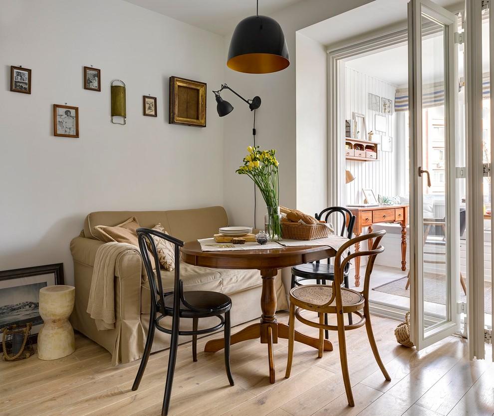 На фото: кухня-столовая в скандинавском стиле с белыми стенами, светлым паркетным полом и бежевым полом с