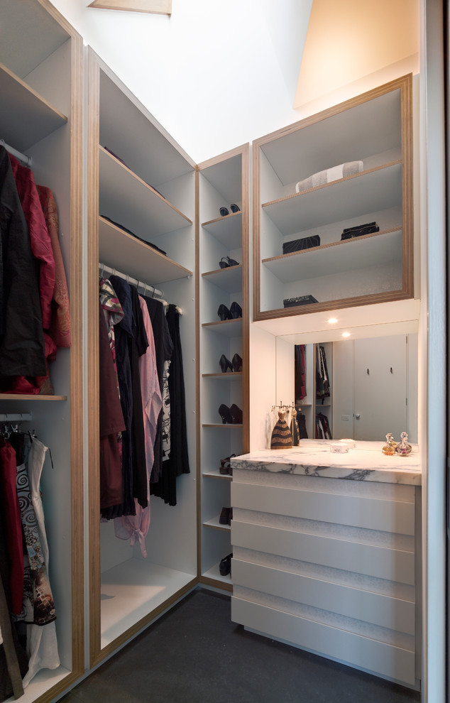 Design ideas for a small contemporary women's walk-in wardrobe in Melbourne with flat-panel cabinets, white cabinets and concrete floors.