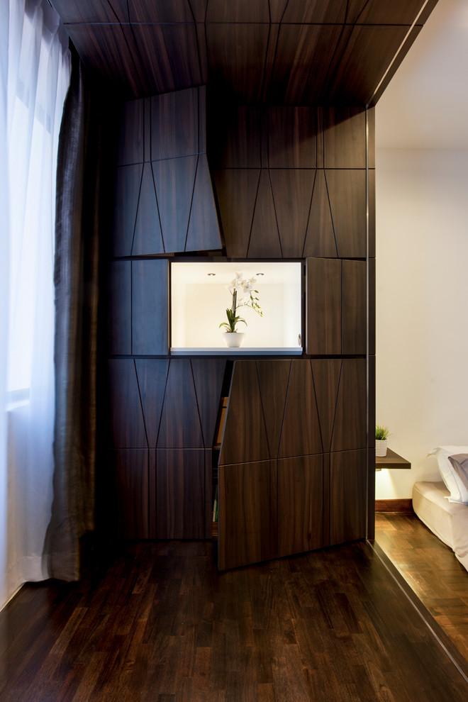 Immagine di un armadio o armadio a muro unisex minimal con parquet scuro, ante lisce, ante in legno bruno e pavimento marrone