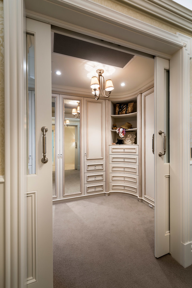 Walk-in closet - large traditional gender-neutral carpeted walk-in closet idea in Perth with recessed-panel cabinets and distressed cabinets