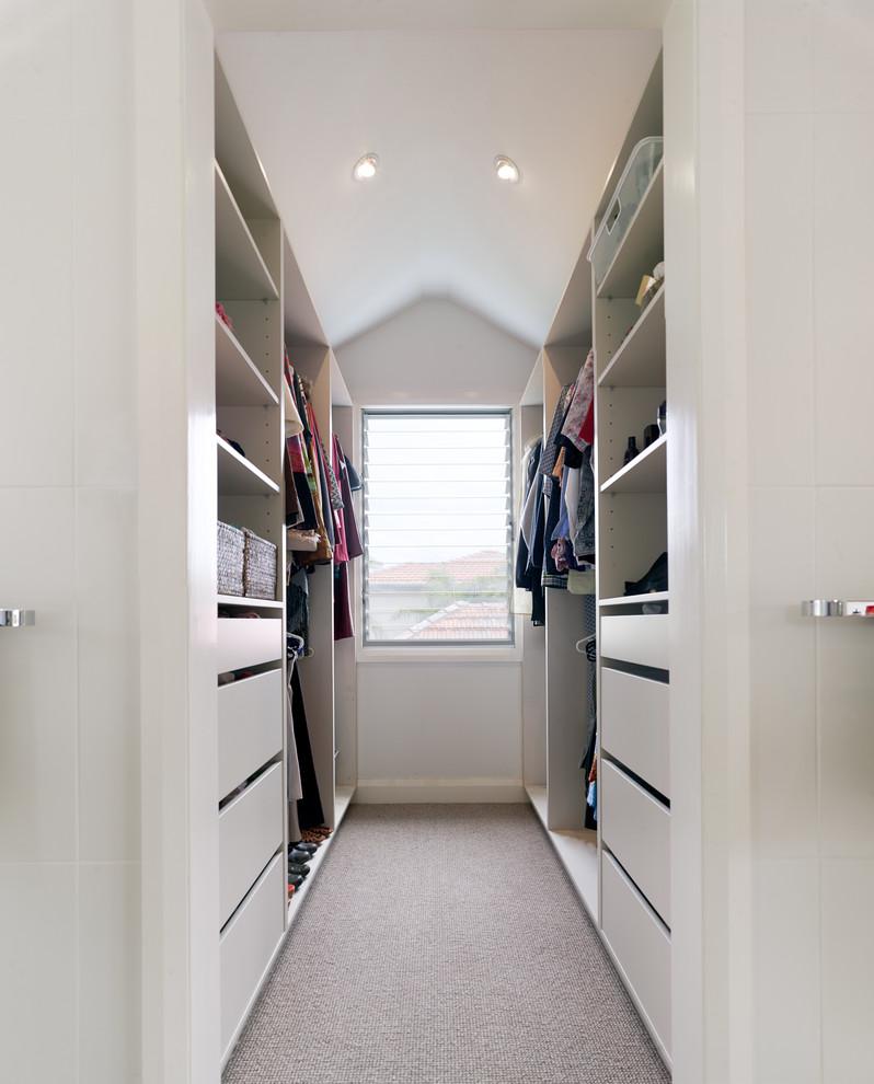 Ejemplo de armario vestidor unisex, actual, de tamaño medio, con armarios con paneles lisos, puertas de armario blancas y moqueta