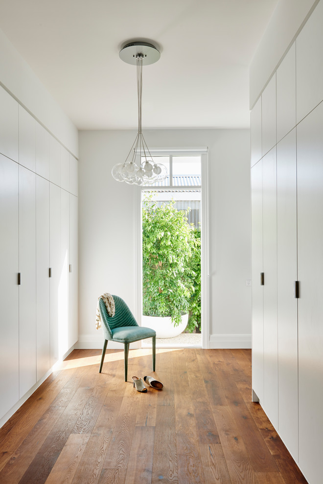 Contemporary women's walk-in wardrobe in Geelong with flat-panel cabinets, white cabinets, dark hardwood floors and brown floor.