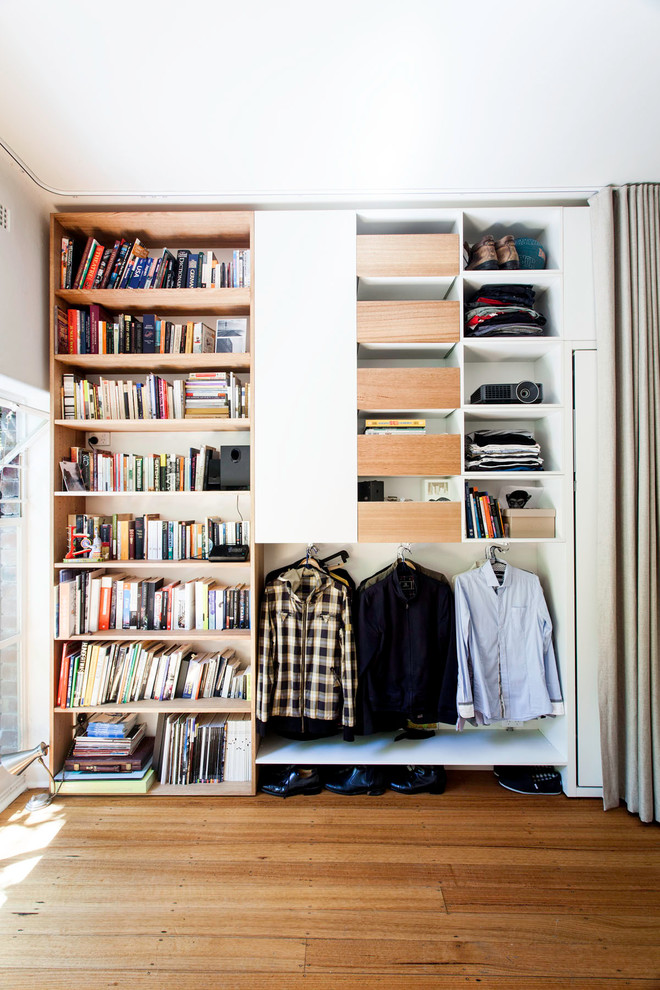 Example of a small trendy men's medium tone wood floor reach-in closet design in Melbourne with open cabinets and medium tone wood cabinets