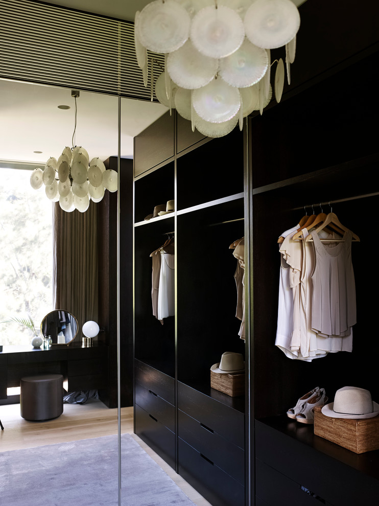 Example of a small trendy gender-neutral walk-in closet design in Sydney with flat-panel cabinets and dark wood cabinets