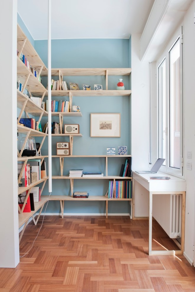 Home office library - mid-sized scandinavian built-in desk medium tone wood floor and brown floor home office library idea in Milan with blue walls