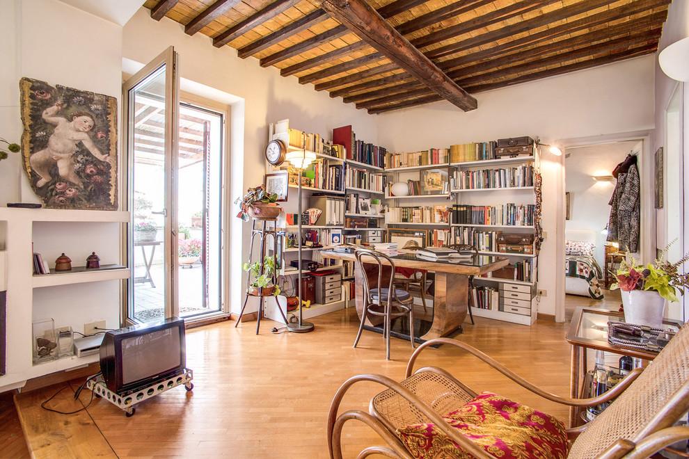 Immagine di uno studio boho chic di medie dimensioni con pareti bianche, pavimento in legno massello medio, scrivania autoportante, libreria e pavimento marrone