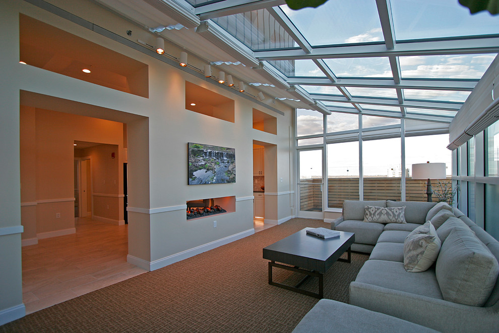 Example of a large transitional carpeted and brown floor sunroom design in New York with a two-sided fireplace and a skylight