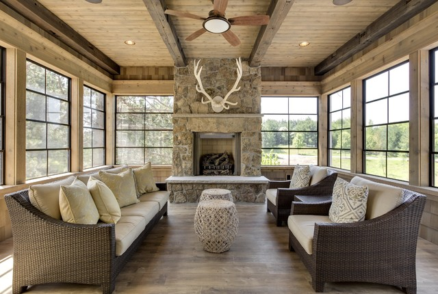 Mid-sized mountain style medium tone wood floor and gray floor sunroom photo in Minneapolis with a standard fireplace, a standard ceiling and a stone fireplace