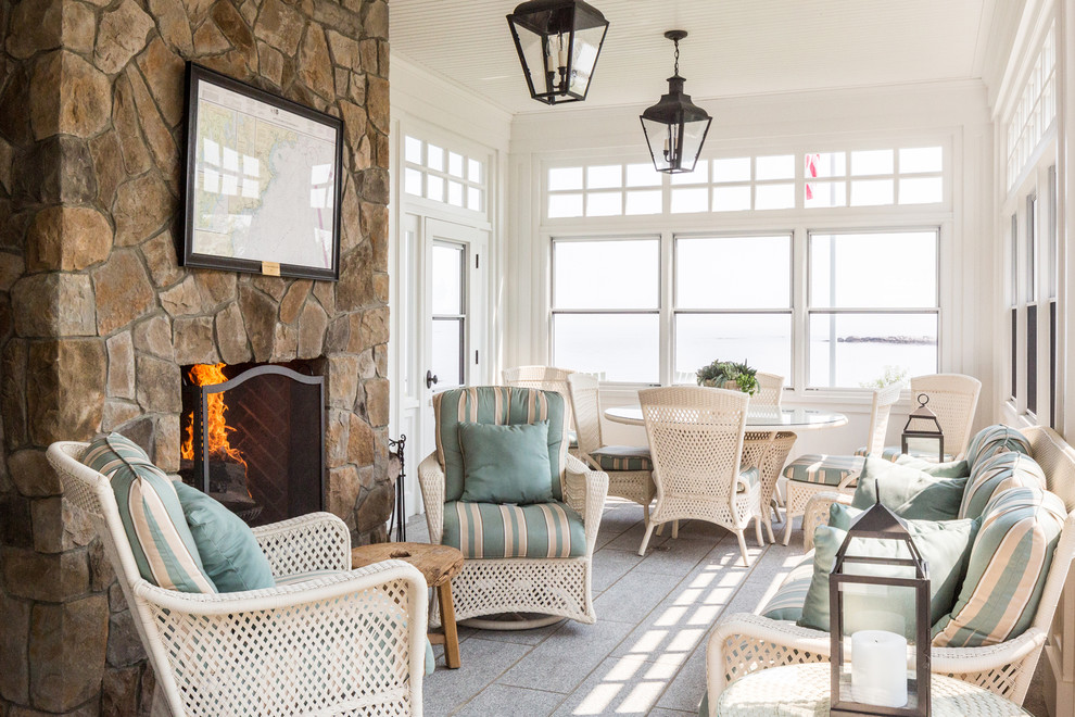Example of a beach style gray floor sunroom design in Portland Maine with a standard fireplace, a stone fireplace and a standard ceiling
