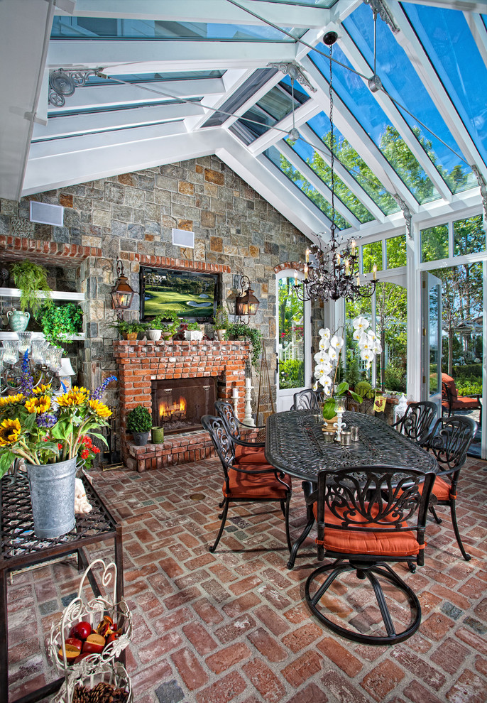 Elegant brick floor and red floor sunroom photo in Orange County with a brick fireplace and a glass ceiling