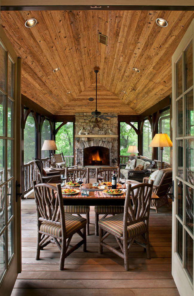 Mountain style dark wood floor and brown floor sunroom photo in Other with a stone fireplace and a standard ceiling