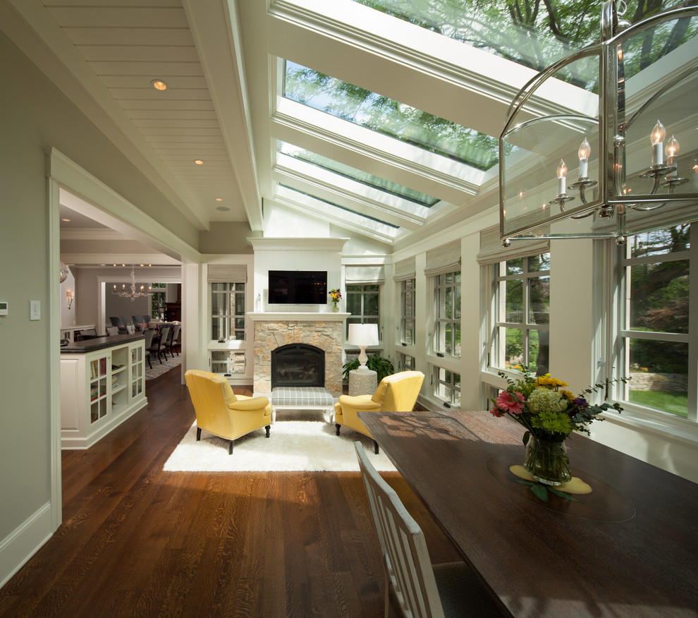 Example of a large transitional medium tone wood floor and brown floor sunroom design in Minneapolis with a stone fireplace, a skylight and a standard fireplace