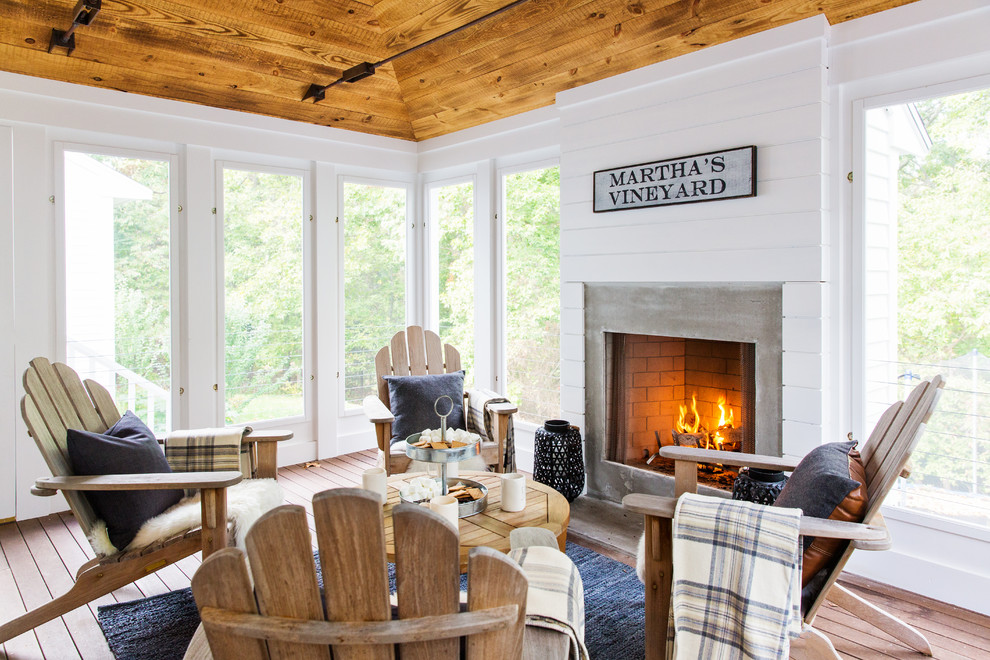 Beach style dark wood floor sunroom photo in Boston with a standard fireplace, a concrete fireplace and a standard ceiling