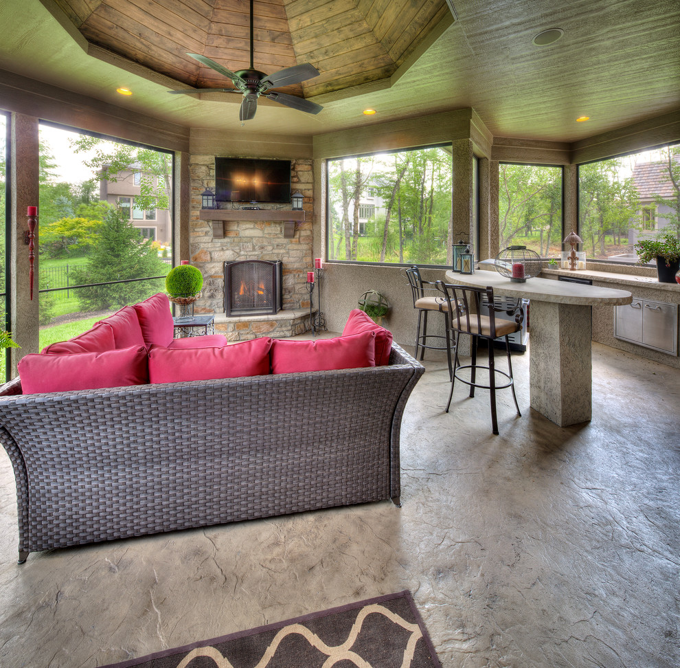 Inspiration for a mediterranean concrete floor and gray floor sunroom remodel in Kansas City with a stone fireplace and a standard ceiling