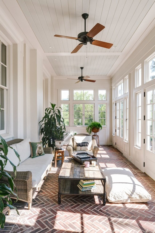 Example of a large classic brick floor and red floor sunroom design in Other with a standard ceiling and no fireplace