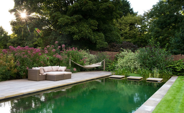 Traditional back rectangular natural swimming pool in Sussex with decking.