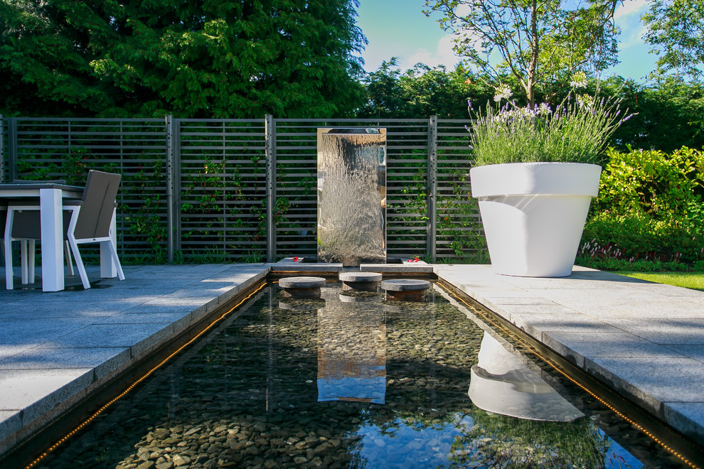Inspiration for a contemporary backyard rectangular lap pool fountain remodel in Manchester