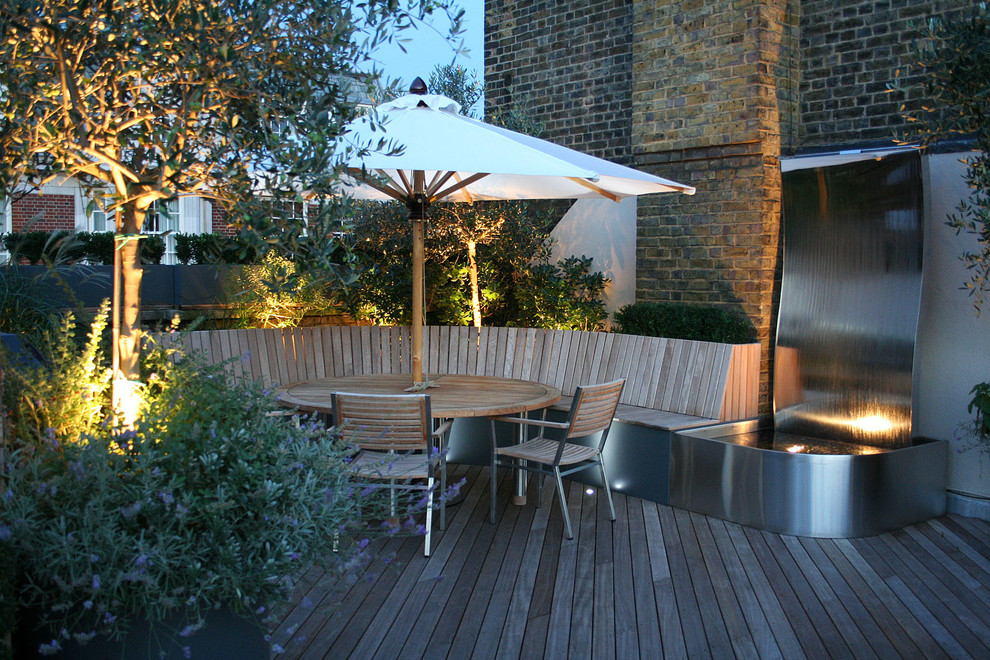 Trendy backyard water fountain deck photo in London with no cover