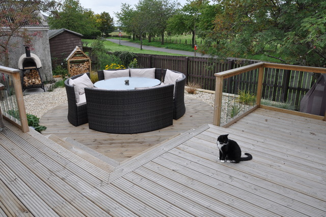 Deck with glass balustrade and steps leading to lower for Decking terrace garden