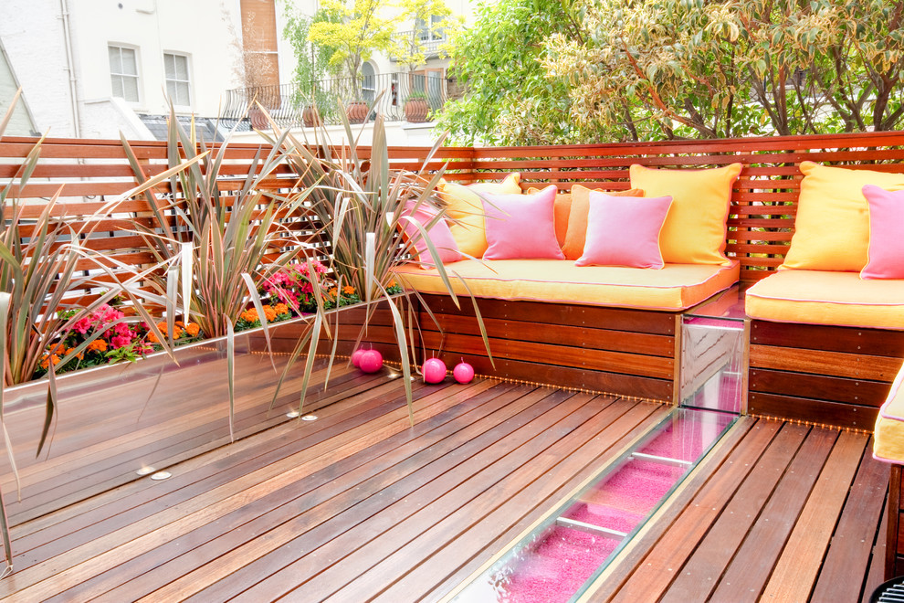 Large trendy backyard deck container garden photo in London with no cover